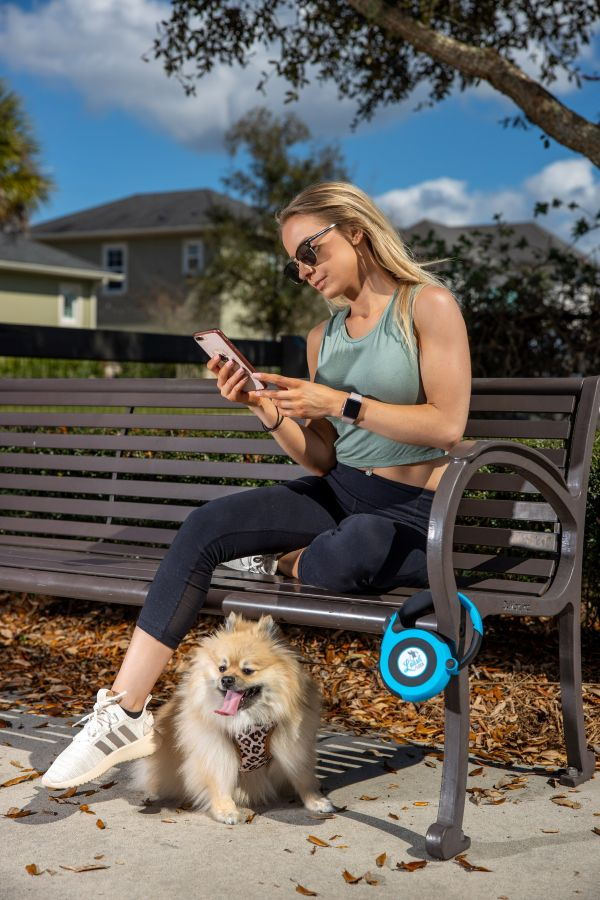 Blonde girl looking at phone while using Leash Lock